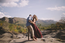 a couple standing on rock in a valley embracing