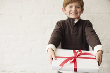 a young boy holding a wrapped Christmas gift