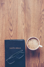 Santa Biblia, reading glasses, and cappuccino