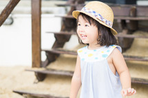 happy little girl in a sunhat on a beach