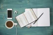 An open Bible, notebook and pencil, coffee, cell phone and ear buds on a green table.