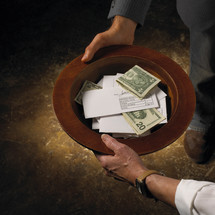 money and envelopes in an offering plate