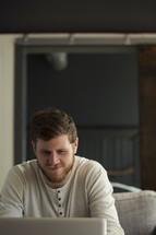 man looking at a computer screen smiling