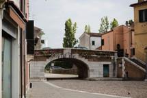 a tunnel under a bridge on a cobble stone street