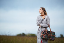 a woman standing in a field holding a purse
