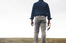 a man standing in a field holding a Bible