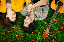 couple lying in the grass and a guitar
