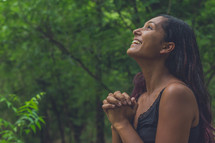 a woman in a forest looking up to God