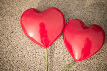 Two red hearts on sticks laying on a textured background