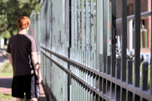 a teen boy standing behind a fence