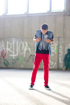 African-American teen boy standing in front of graffiti covered wall.