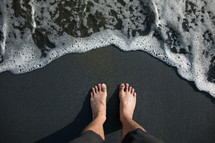 bare feet standing on a shore at the edge of the water