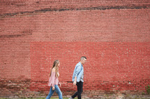 a couple walking holding hands in front of a red brick wall