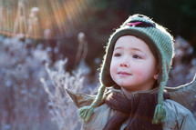a toddler boy standing outdoor in winter