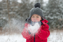 a boy child blowing snow