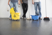 volunteers with paint brushes, mops, and brooms