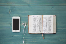 iphone 6 and earbuds and open Bible on a teal table