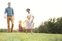 Mixed family walking and playing outdoors at sunset.