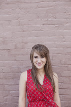 smiling young woman standing in front of a wall