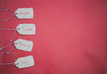 """Christmas gift tags reading """"Hope,"""" """"Love,"""" """"Peace,"""" and """"Joy"""" on a red background."""
