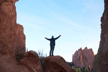 a man standing on a mountain with raised arms