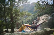 a woman in a hammock next to a tent in a campsite