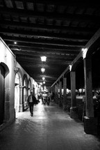 people walking under a covered walkway at night