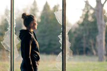 a teen girl standing in a broken window