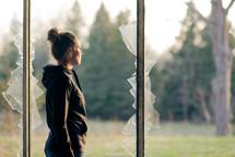 a teen girl standing in a broken window