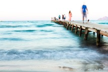 people walking on a small wooden pier