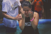 A young woman rises from a baptismal pool.