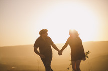a couple walking holding hands at sunset