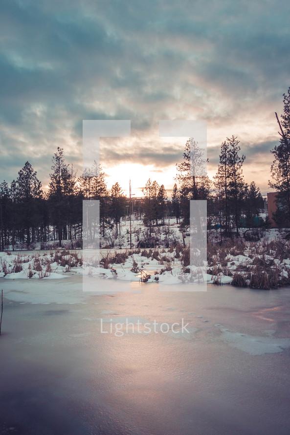 frozen pond at sunset