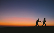 the silhouette of a couple running holding hands at sunset