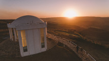 a couple holding hands walking down steps of an observatory  at sunset