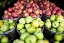 green and red apples in baskets