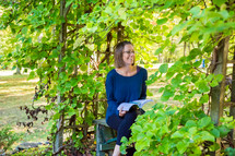 a woman sitting on a bench reading outdoors