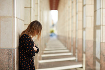 a woman looking down standing alone in a hallway