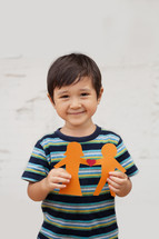 Concept of family with Asian Preschool-aged boy holding up a paper people chain of a traditional couple with a heart in between them.