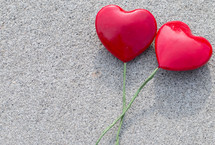 Two Solid Red Hearts with Green Stems on a textured background