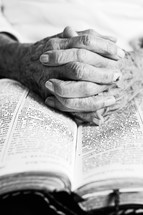 Elderly hands interlaced on an open bible.