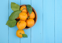 bowl of oranges on a blue table