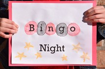 A girl holding a Bingo Night sign