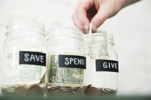 placing money in Give, Save, Spend money jars