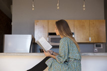 a woman in her pajamas reading in the kitchen with coffee