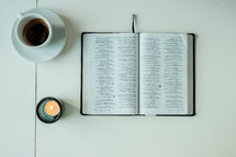 coffee cup, open Bible, votive candle, pages