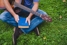 young man sitting in grass playing a guitar and holding a Bible