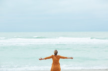 a woman standing on a beach with open arms