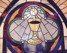A stained glass window depicting the Eucharist