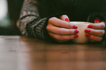 a woman with painted nails holding a coffee mug